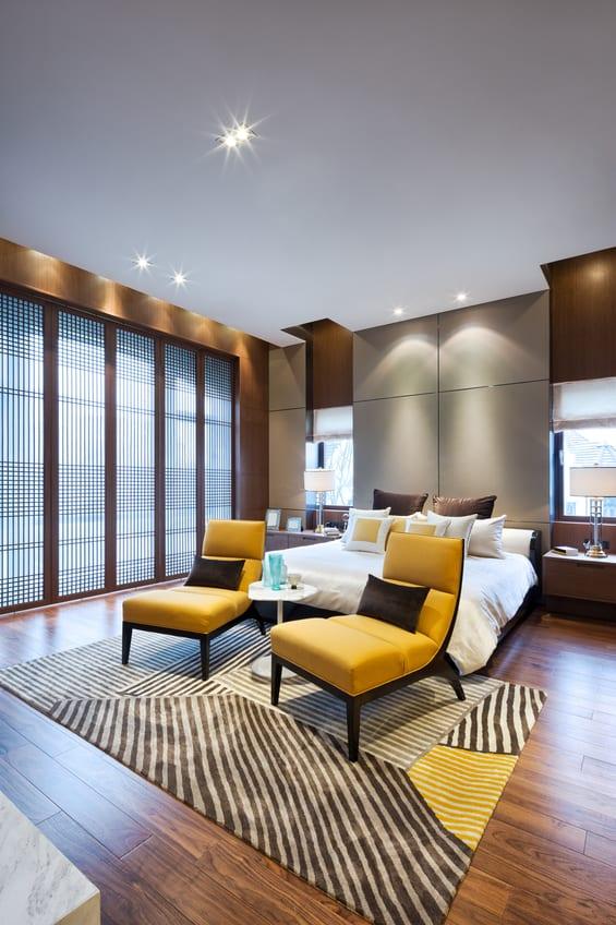 modernes schlafzimmer interior mit holzfußbodenbelag, holzwandverkleidung, grauer akzentwand hinter boxspringbett, gelbe lounge-sessel auf teppich mit zebra-muster und deckeneinbaustrahlern