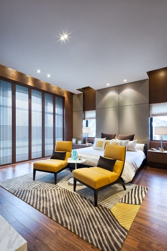 Modernes Schlafzimmer Interior Mit Holzfußbodenbelag, Holzwandverkleidung,  Grauer Akzentwand Hinter Boxspringbett, Gelbe Lounge