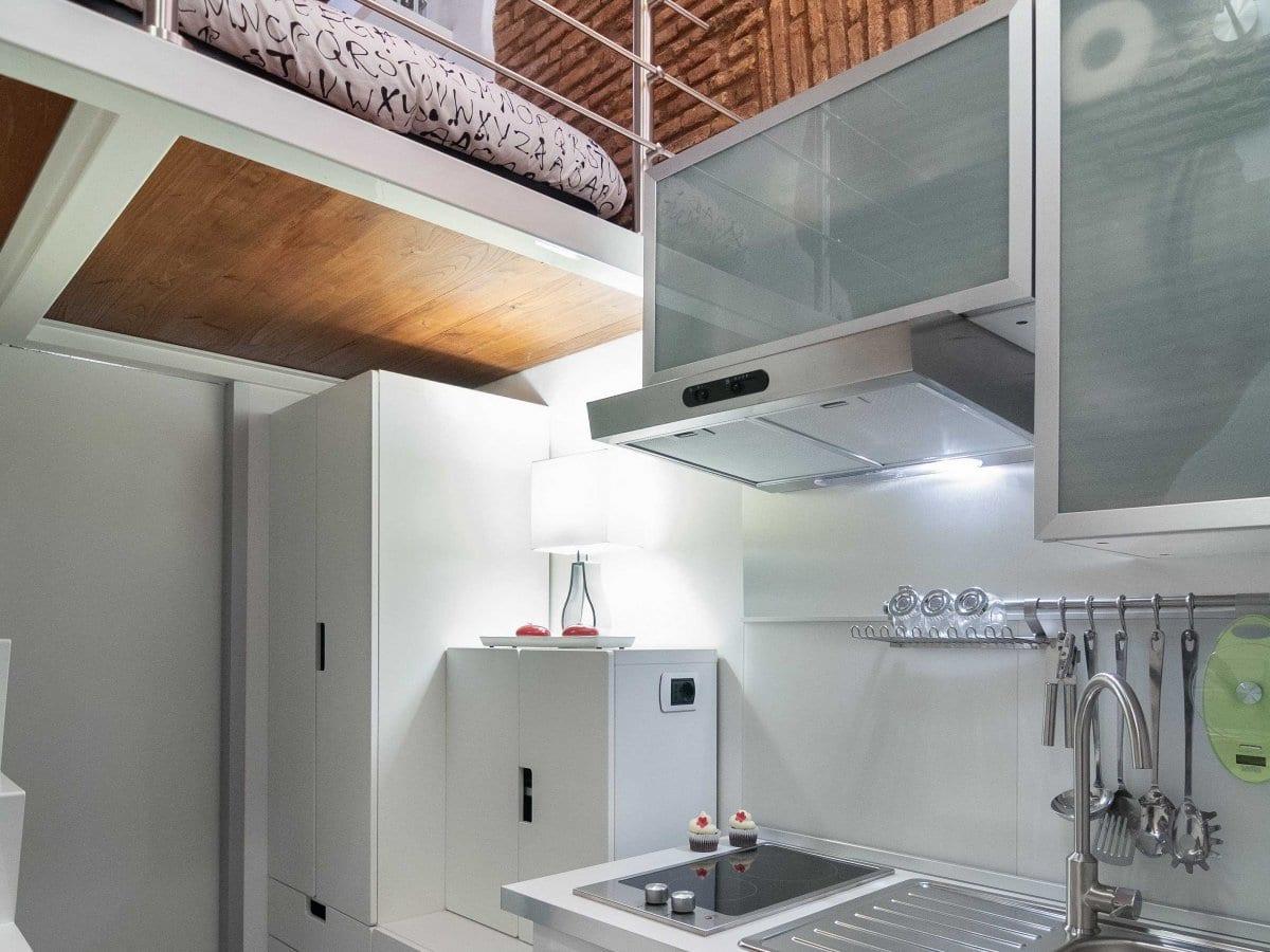 kleine loftwohnung mit weißen schränken, authentischen Ziegelwänden und loftbett auf metallkonstruktion mit dunklem holzfußbodenbelag