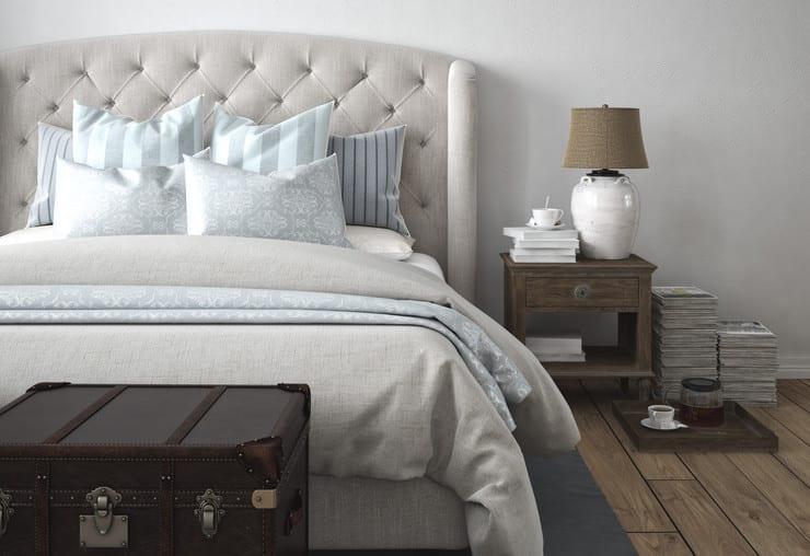 schlafzimmer gestalten mit boxspringbett beige mit gepolstertem bettkopfteil, rustikalem nachttisch holz, altem lederkoffer vor dem bett und holzfußbodenbelag