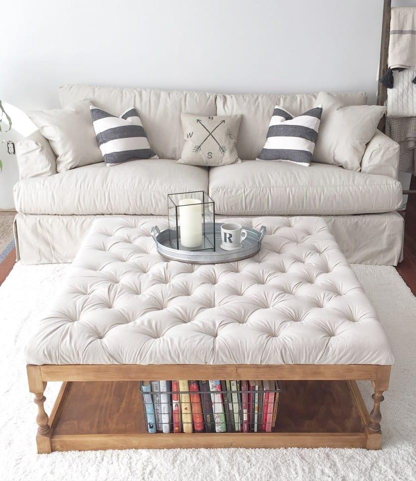 kleines wohnzimmer modern einrichten mit weißem sofa und DIY couchtisch mit polster als bücherregal