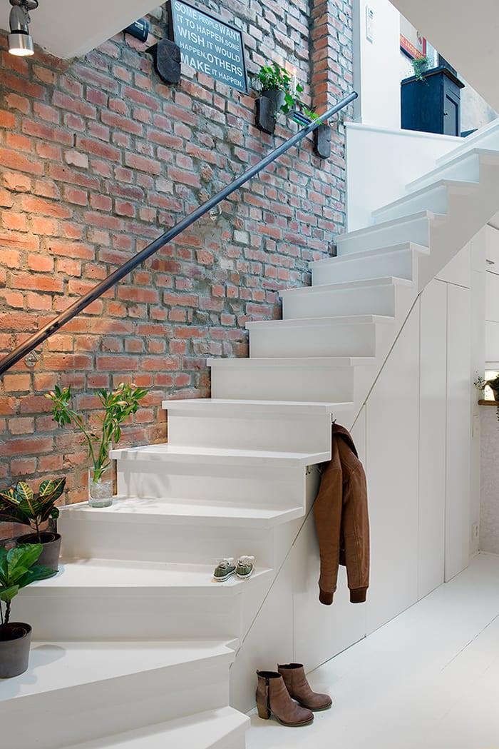 coole raumkonzepte mit ziegelwand und weißer Kleiderschrank-Treppe_moderne maisonette mit platzsparender Einrichtung und cooler Wandgestaltung