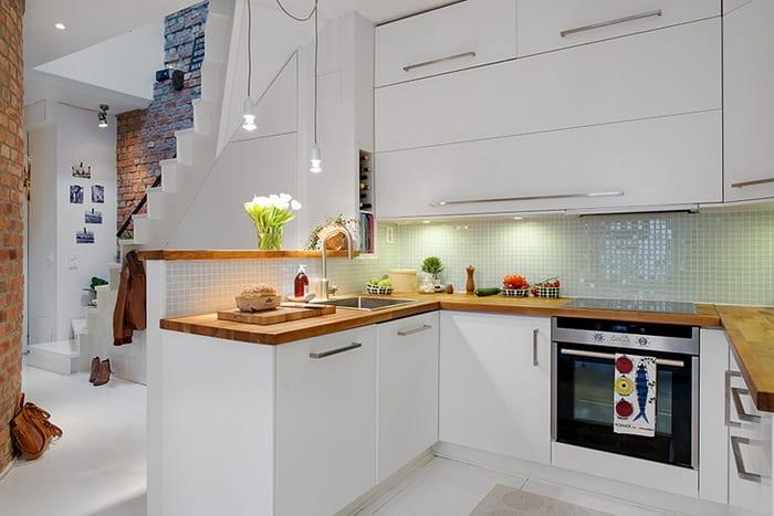 moderne weiße küche mit granitküchenplatte in Holzoptik, weißen Wandschränken mit klapp-schranktüren und küchenrückwand aus weißer Glasmosaik als einrichtungsidee für offene küchen in maisonette