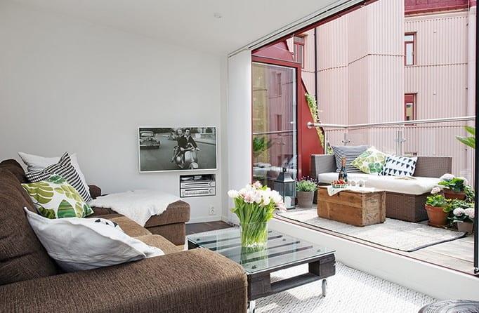 maisonette wohnung mit kleinem wohnzimmer und ausganz zur dachterrasse_coole raumgestaltung mit ecksofa, palettentisch auf rollen und wandmontiertem TV-gerät