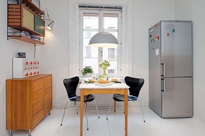 essplatz in der küche mit weißem boden, holzesstisch mit schwarzen holzstühlen und sideboard holz mit klassischem wandregal holt
