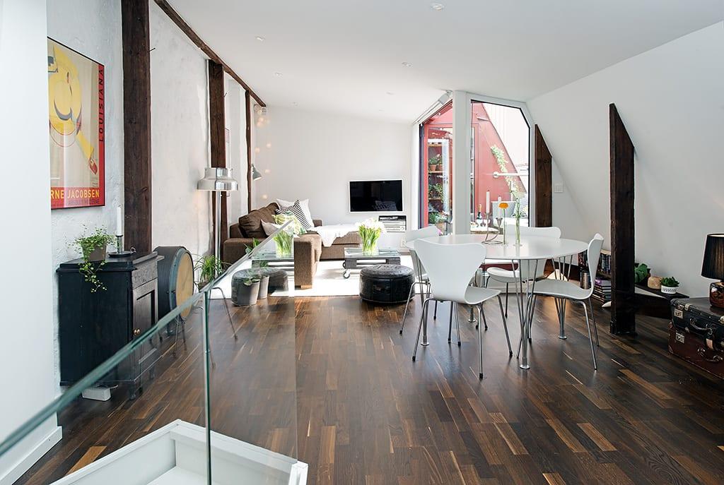 modernes wohn esszimmer mit dunklem parkett, holzbohlen, weißem esstisch rund und niedrigen holzwandregalen als wandgestaltung