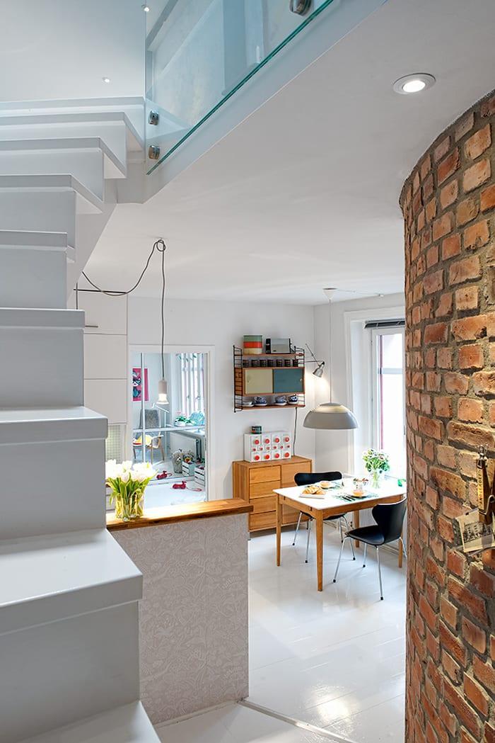 maisonette wohnung mit offener Küche unter schmaler Innentreppe in weiß _moderne raumgestaltung mit weißem holzfußboden und ziegelwänden