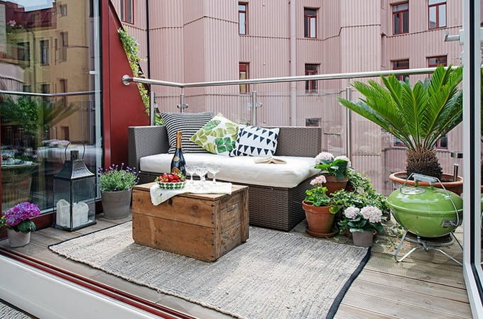 coole dachterrasse und terrassengestaltung mit tagesbett grau, DIY kaffeetisch aus holz auf teppich, Laterne schwarz und frischen blumen