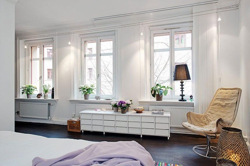schlafzimmer gestalten mit dunklem holzfußboden, weißer kommode aus holz_weiße fensterbank dekorieren mit frischen blumen und tischlampe
