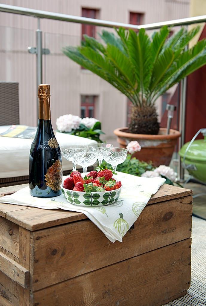terrasse effektvoll gestalten mit diy couchtisch_idee für sommerpartys auf die terrasse mit Erdbeeren und flasche Champagner