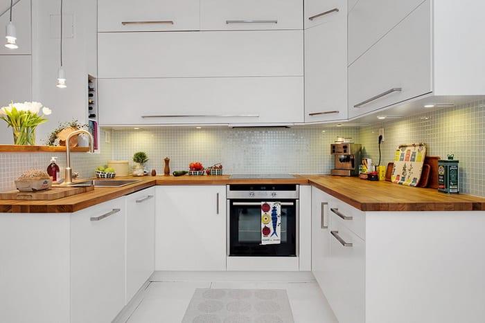 maisonette einrichtungsideen_weiße küche mit u-förmiger küchenarbeitsplatte aus holz und kleiner theke hinter Spülbecken mit weißen pendellampen und frischen blumen