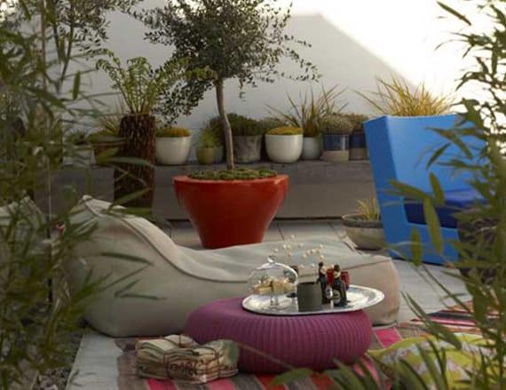 garten idee für moderne gartengestaltung mit Polster-Lounge in blau und beige und rote blumenkübel