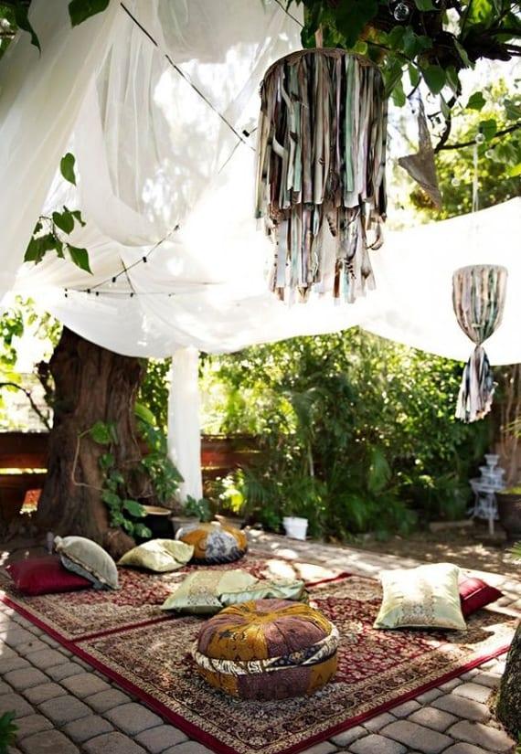 gartengestaltung im boho style mit weißem baldachin über orientalischer sitzecke von teppichen und sitzkissen