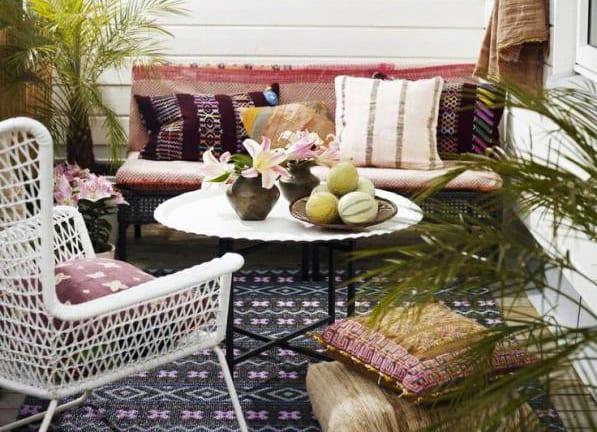 inspiration für terassengestaltung mit terrassenmöbeln aus rattan, dekokissen und gemustertem teppich
