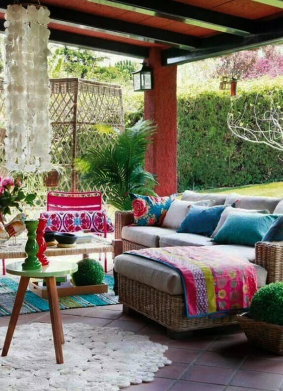 bohemian terrassengestaltung mit rattan-ecksofa,rattan-blumenkubel, blauen kissen und teppich und holzckoer grün mit farbigen kerzenhaltern