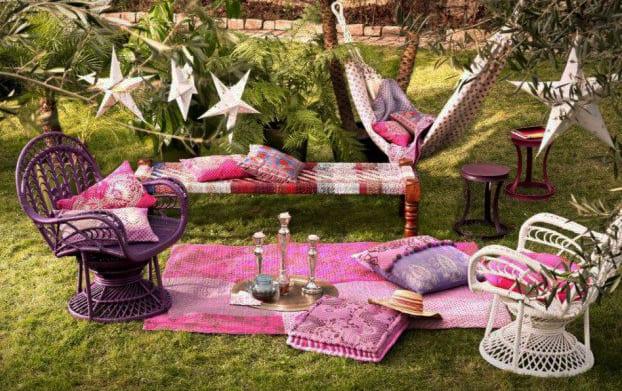 kreative idee für boho garten im lila mit rosafarbigem teppich, gemusterter hängematte und holzarmstühlen in weiß und lila
