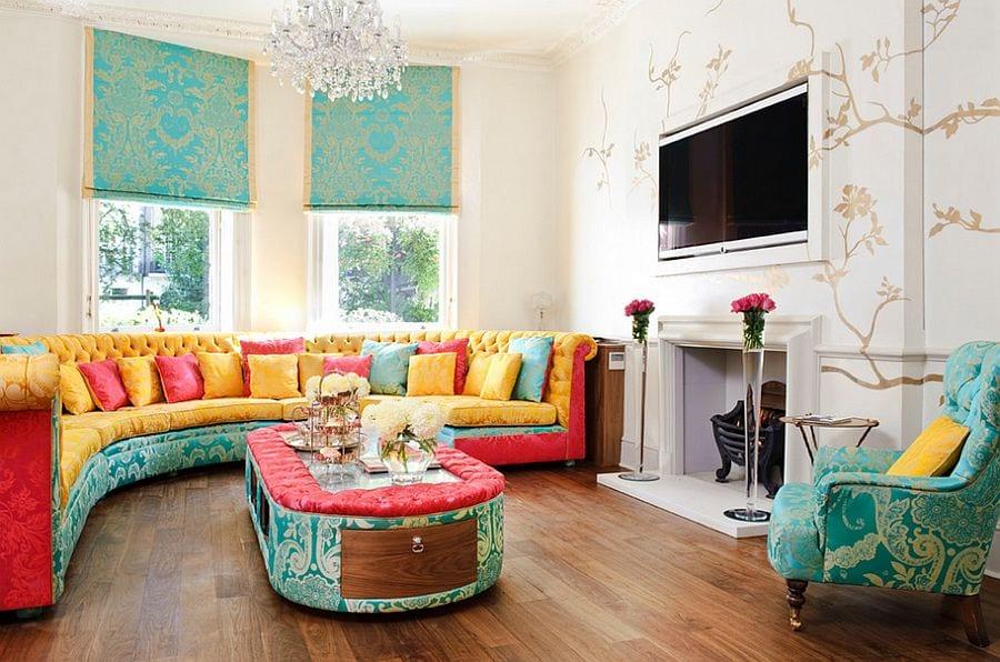 kreatives wohnzimmer design mit tvwandpaneel über dem kamin, wandtattoo in beige, blauen fensterrollos und rundem sofa mit ottomanentisch in pink, gelb und blau