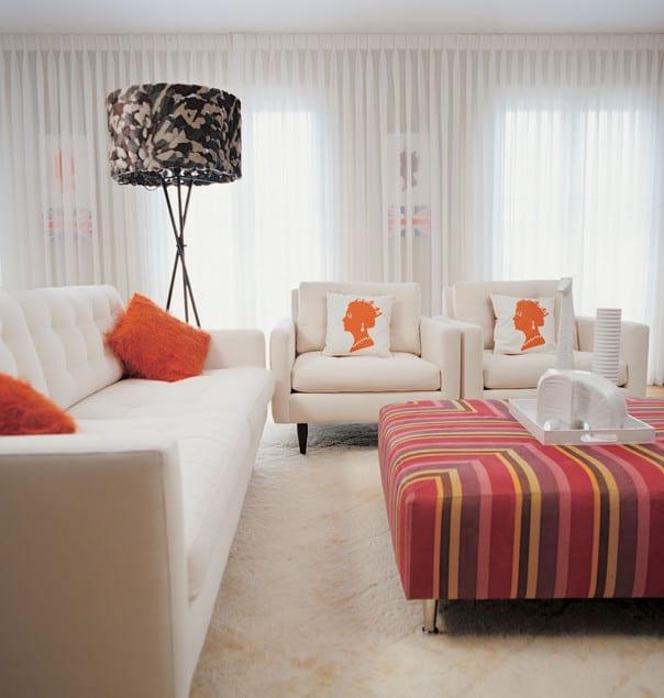 modernes wohnzimmer weiß mit weißen seats and sofa und rosafarbige Ottomane mit streifenmuster als Farbakzent