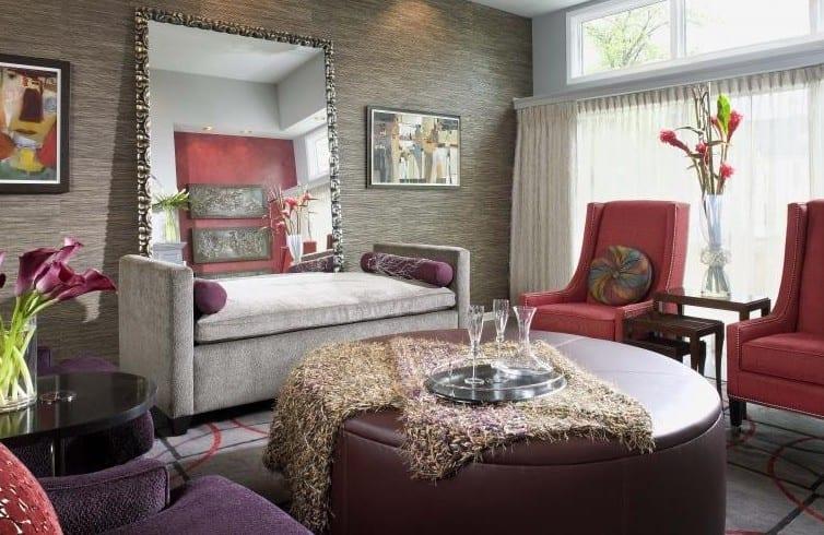 modernes wohnzimmer mit grauer Tapete, graues tagesbett vor Spiegel, rosafarbige Armsessel auf grauem teppich