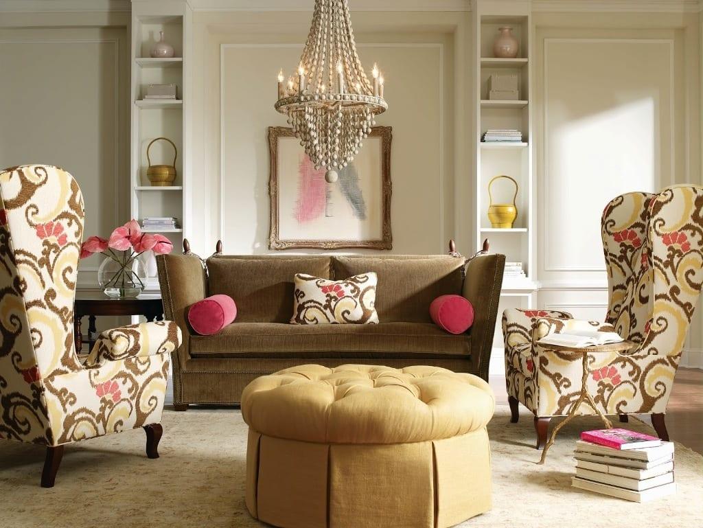 klassisches wohnzimmer design mit gemusterten armsesseln, braunem Sofa und rundem Polsterhocker gelb