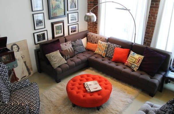 wohnzimmer mit ziegelwänden einrichten mit sofa braun und runde ottomane in rot auf weißem hochteppich