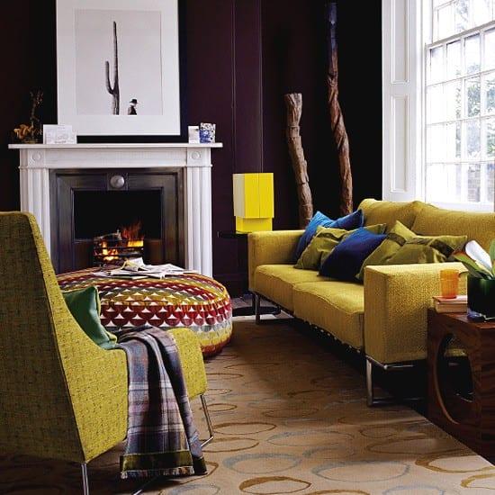 wohnzimmer idee für wohnzimmergestaltung mit wandfarbe schwarz, weißem kamin und gelben sofa und polster-kaffeetisch rund