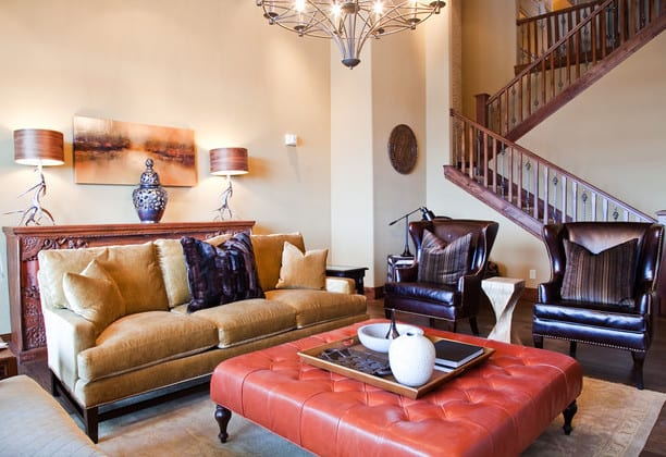 wohnzimmer design in klassischem Stil mit Leder-ottomane,leder-armsesseln und rustikalem sideboard aus holz hinter gelbem sofa