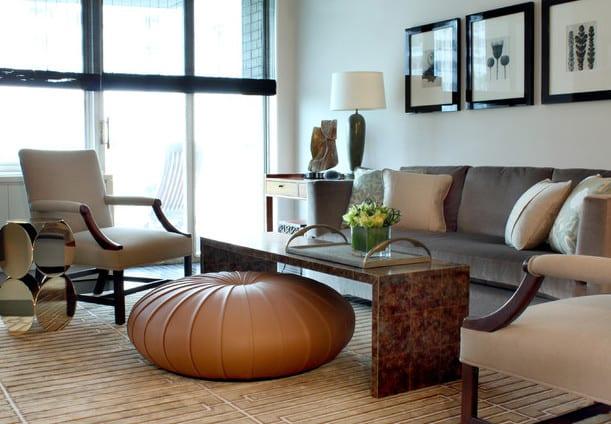 modernes wohnzimmer mit grauem Sofa aus Plüsch, couchtisch aus fliesen und runder Ottomane als beistelltisch