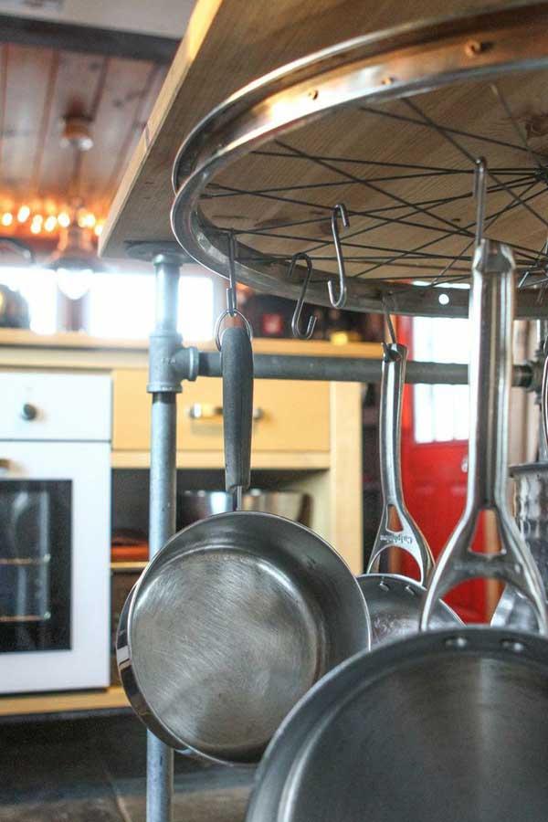 kreative idee zum platzsparen in der küche mit diy esstisch holz mit darunter aufgehängte fahrradfelge zum aufhängen von kochgeschirr