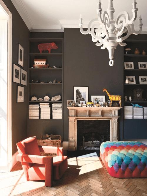 coole beispiele für moderne wohnzimmer und kreative farbgestaltung mit wandfarbe schwarz_wohnzimmer mit parkett, kamin, bunte Ottomane und schwarzen eingebauten wandregalen