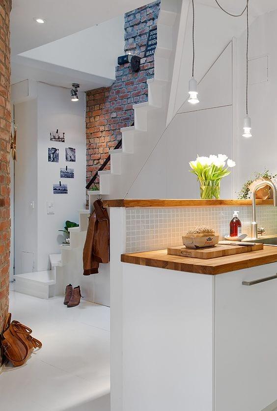 kleine loft wohnung modern einrichten mit weißer küche und trennwand als schmale Theke und küchenrückwand aus mosaik
