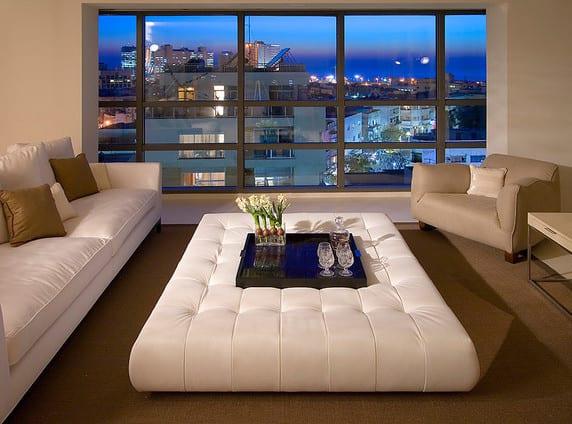 ideen für wohnzimmer design mit weißen sofau und ottomane mit tablett auf teppich in beige vor verglasung mit blick auf die Stadt