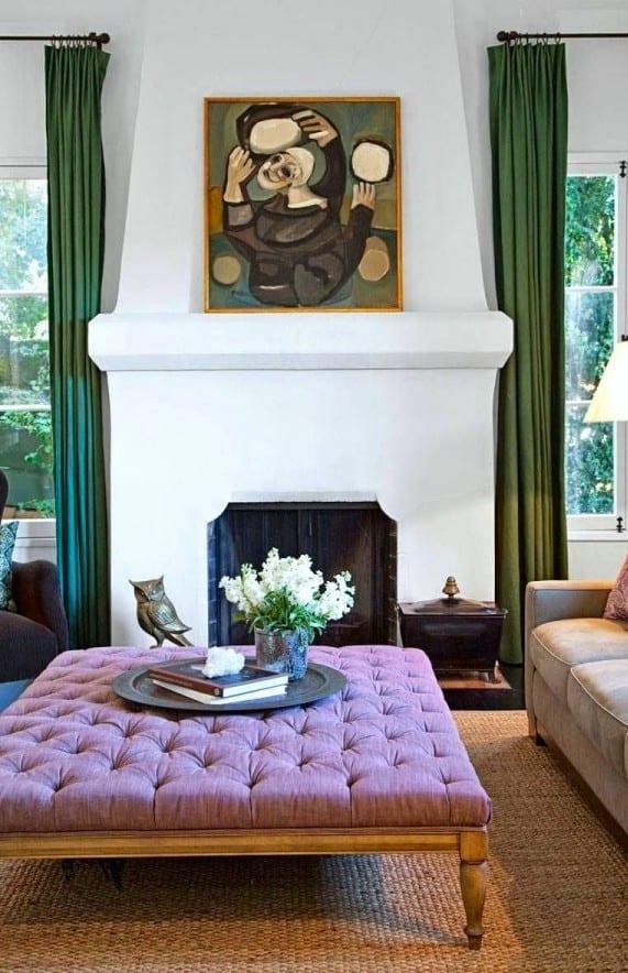 wohnzimmer mit kamin, grünen vorhängen und lila couchtisch zwischem sofa und schwarzen Polstersesseln