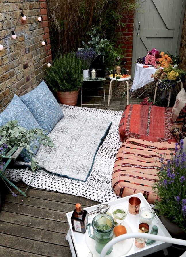 kleine holzterrasse oder hofgarten mit ziegelwänden gestalten im boho style mit kissen, vorleger und viele hockern als beistelltische und blumengestell