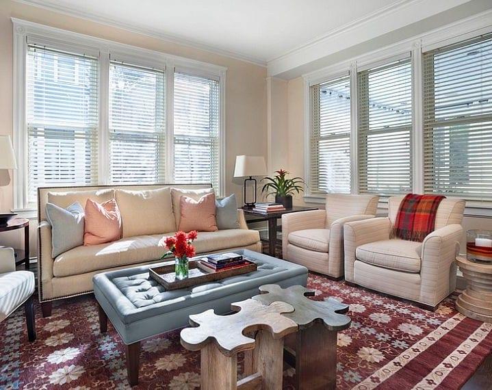 wohnzimmer inspiration mit blauer Ottomane auf rotem Teppich mit blumen und cremefarbige Sofa dekoriert mit kissen in hellblau und hellrosa