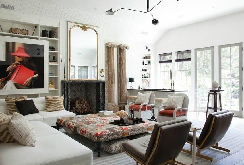 modernes wohnzimmer mit weißem ecksofa, ottoman-polstertisch und schwarzen ledersesseln vor schwarzem kamin mit großem spiegel und zwei grichischen säulen als wandgestaltung