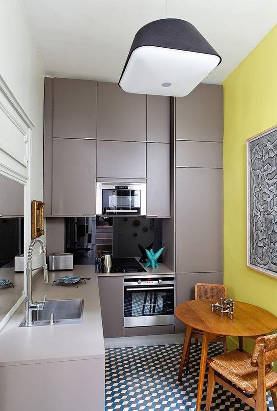 inspiration für moderne wohnküche und kleine küche einrichten mit gelber wand, schwarzweißen bodenfliesen, rundem holzesstisch und spiegel hinter spülbecken