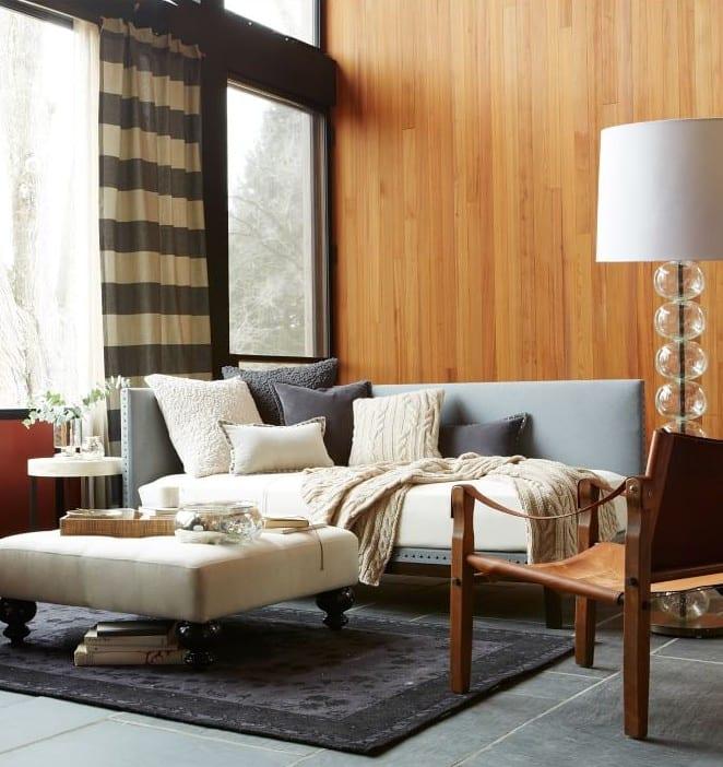 wohnzimmer interior mit holzwandverkleidung, dunklem steinbodenbelag und modernen Ottomanen als Sofa und kaffeetisch