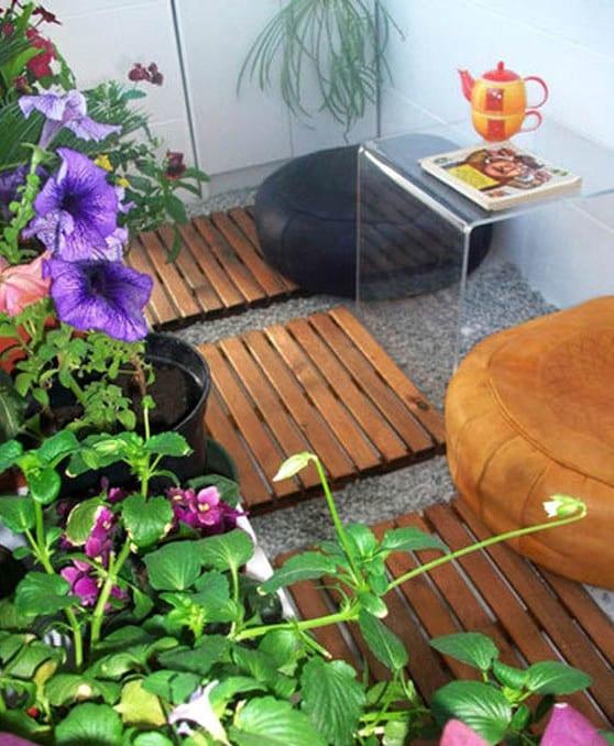 balkon ideen für balkongestaltung mit holz-fliesenauf kies, kaffeetisch aus acrylglas und runden ledersitzkissen