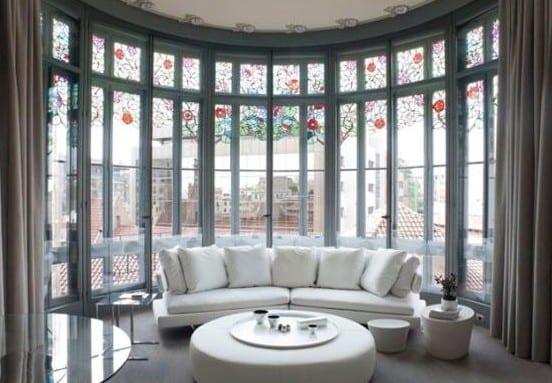wohnzimmer mit gerundeter fensterband, ledersofa weiß und leder-couchtisch rund