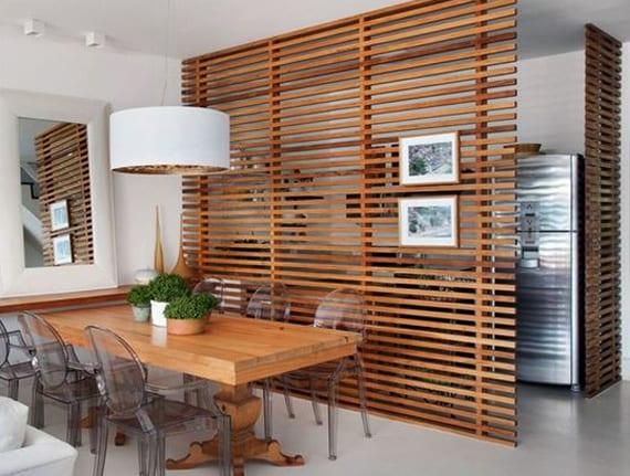 modernes wohnesszimmer mit massivholzesstisch und esstischstüle aus acrylglas modern gestalten mit wandspiegel in weißem spiegelrahmen und trennwand aus holzlatten