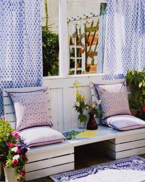 holzterrasse gestalten mit blauen gardienen und diy gartenbank weiß mit tisch und lilafarbigen Kissen
