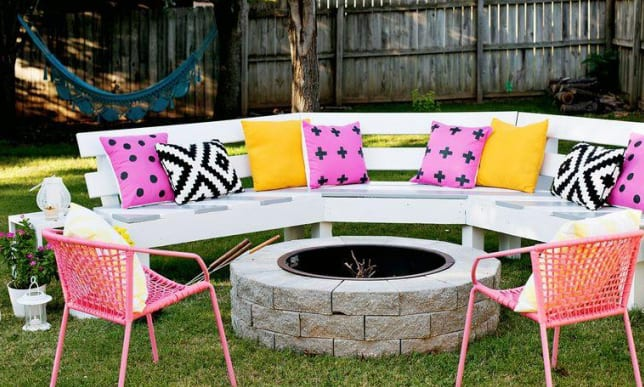 gartengestaltung mit diy gartenbank weiß und runde feuerstelle aus steinen und rosafarbige gartenstühlen
