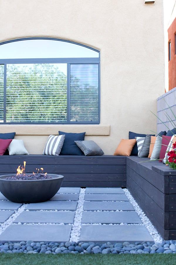 schwarze eck-gartenbank aus holz mit runder feuerstelle aus beton als idee für moderne terrassengestaltung