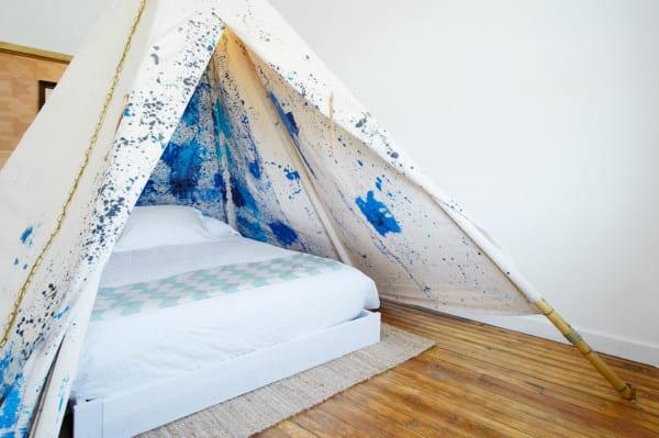 schlafzimmer design mit holzfußbodenbelag und diy zelt aus bambusröhren und weißem Textil mit blauen Farbflecken