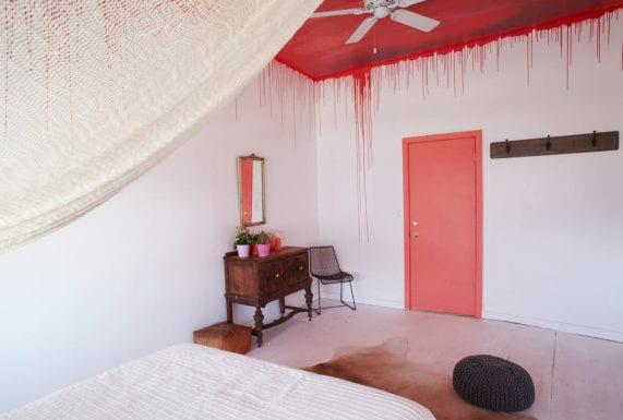 interessantes schlafzimmer inspiration mit roter decke und tür, holzkommode im barock style, kuhfellteppich und hängematte über dem bett_coole streich idee für weißes schlafzimmer