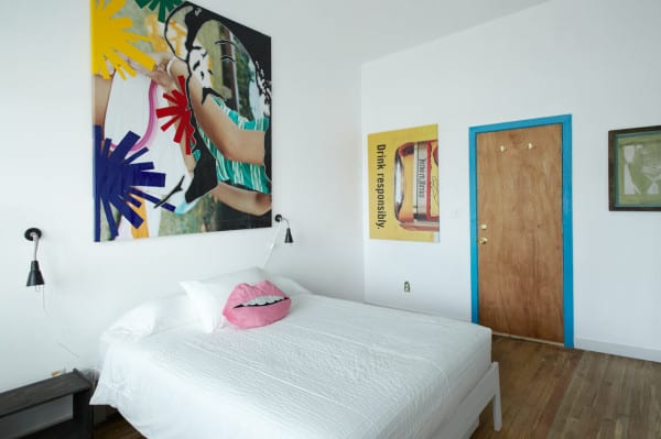schloafzimmer weiß mit blauem türrahmen und wanddeko mit Plakate und collage