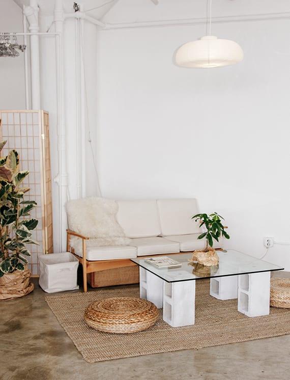 modernes wohnzimmer in weiß und holz mit poliertem estrichbodenbelag, rattan Puffs und diy couchtisch