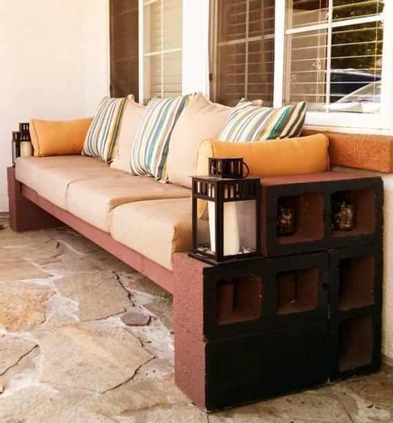 terassengestaltung mit steinbodenbelag und diy sitzbank aus braun geschtrichenen kanthölzern und betonblöcken, polsterkissen beige und zwei laternen aus metall