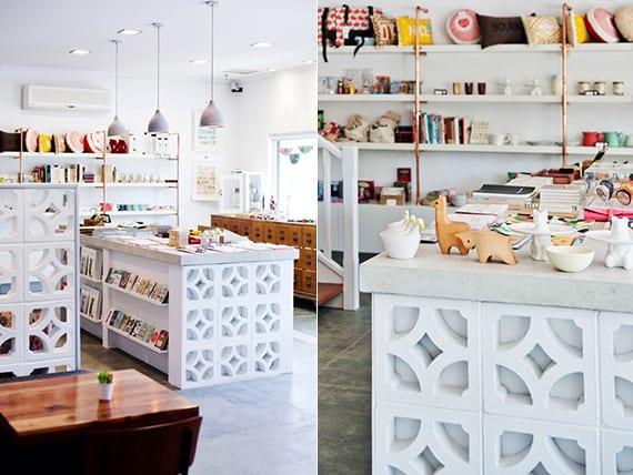coole raumgestaltung mit weißen betonblöcken als verkleidung von bartheke_modernes interieuer in weiß mit beton-pendellampen, diy wandregalen aus messing rohren und gemusterten betonblöcken